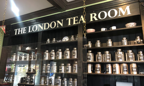 """A black-painted shelf behind a counter, containing steel containers of tea. The words """"The London Tea Room"""" are written at the top of the shelf."""