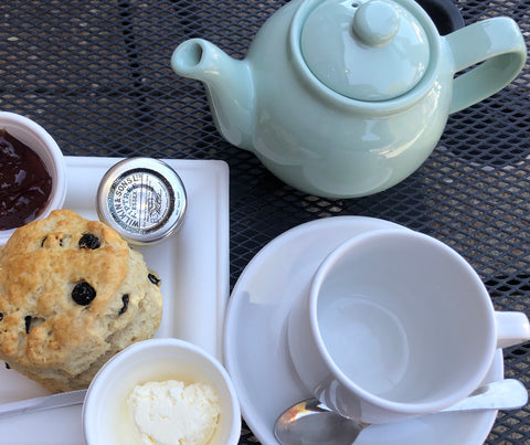 A single-serving light blue teapot on a black table. In front of the teapot is an empty white teacup with a saucer and spoon. Next to the cup and saucer is a scone with raisins, jam, and clotted cream on a square plate.