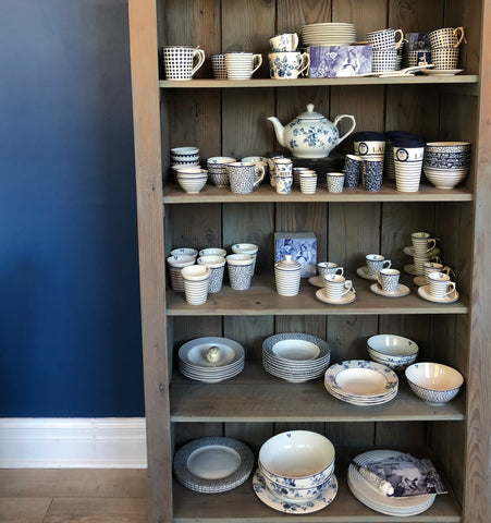 A gray-green wooden shelf filled with teaware. All teaware is blue and white. The top shelf contains cups and saucers with varying designs, the second shelf contains a floral teapot surrounded by cups and bowls. The center shelf contains espresso-sized cups and saucers. The two bottom shelves contain bowls.