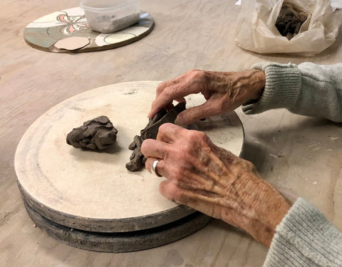 Paddy's hands molding dark clay on a pottery wheel.