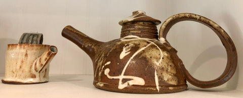 A ceramic teapot with a large handle, spackled with multiple colors.