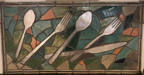 A stained glass mosaic with spoons, forks, and knives.