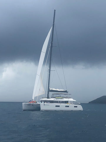 A small white sailboat at sea. The sky is cloudy and overcast.