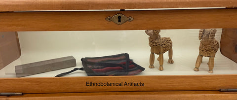 Artifacts behind glass. These include woven animal statues, a travel bag, and a long rectangular box.