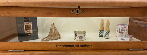 Artifacts behind glass. These include what appear to be small books, a tin can, some bottles, and a woven hat.
