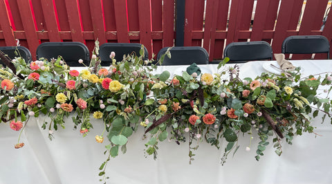 A long table covered in a white tablecloth with a row of black chairs behind it. On top of the table is a display of white, red, and yellow flowers.