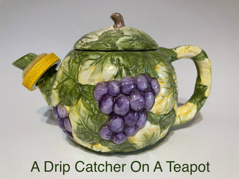 A ceramic teapot with a drip catcher shaped like a slice of lemon. The teapot is painted with a pattern of leaves and grapes, and the caption reads 'A Drip Catcher On A Teapot'.
