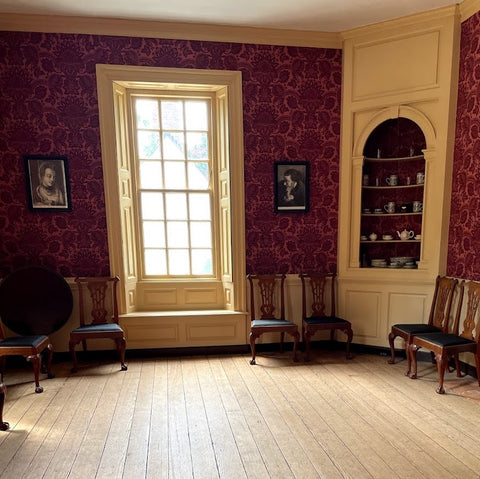 An elegant room with red, patterned wallpaper and a wood floor. Decorative chairs are arranged around the perimeter of the room. A tea table sits in the corner. In the other corner is a shelf with ceramic teaware.