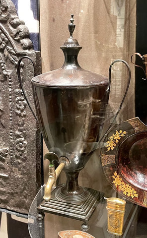 A metal tea urn with handles on either side and a raised base.