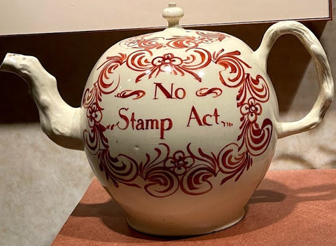 A white ceramic teapot decorated in dark red flourishes. In the center is painted the words \'No Stamp Act\' in red.