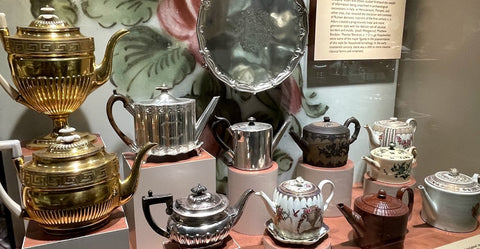A collection of bronze, tin, ceramic, and earthenware tea pots. 11 teapots are shown.