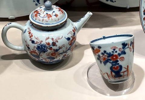 A Chinese-style ceramic teapot and matching cup. The cup does not have a handle. Both the cup and pot are white and decorated with red and blue floral designs.