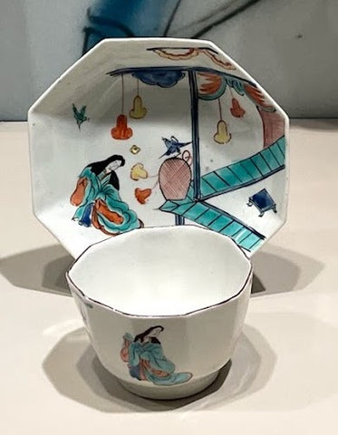A Japanese-style cup and saucer. The saucer has a hexagonal shape, and the cup has no handle. Both the cup and saucer depict a woman in traditional attire. The saucer also includes images of birds and flowers.