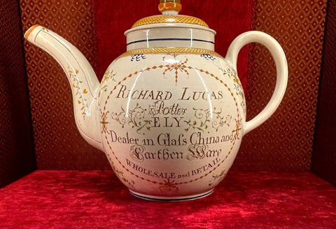 A very large ceramic teapot. The color is off-white and decorated with a tan and blue design. On the teapot is written: \'Richard Lucas, Potter, Ely, Dealer in Glass, China, and Earthenware. Wholesale and Retail.\'