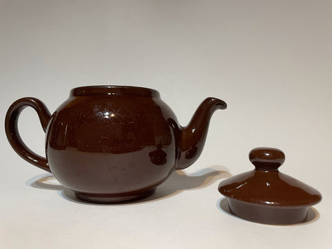 A Brown Betty teapot without a lid against a plain white background. The lid is next to the teapot and has a round handle. It has a shiny glaze and a dark brown color.