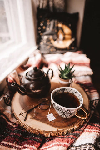 A teapot, teacup, pair of glasses, and small houseplant on a wooden tray. The tray is resting on a woven blanket next to a window, where light is streaming in. The teapot is a small Brown Betty Teapot. The teapot has a black-and-white pattern with a gold handle and is filled with black tea.