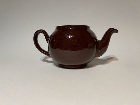 A Brown Betty teapot without a lid against a plain white background. It has a shiny glaze and a dark brown color.