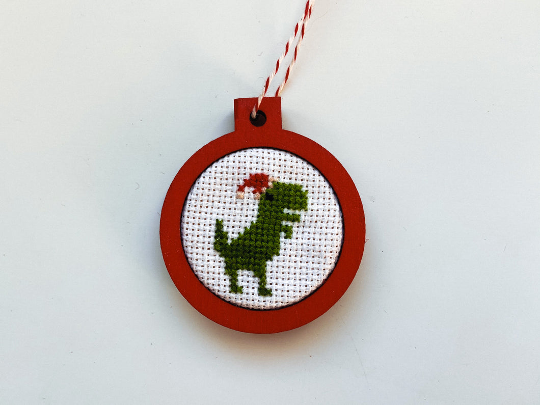 Dinosaur in Santa hat ornament in red wood frame
