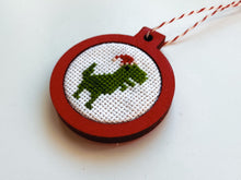 Load image into Gallery viewer, Dinosaur in Santa hat ornament in red wood frame