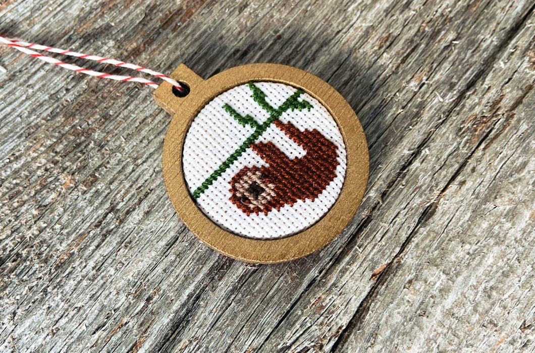 Hand-stitched brown sloth hanging from branch in small wooden frame