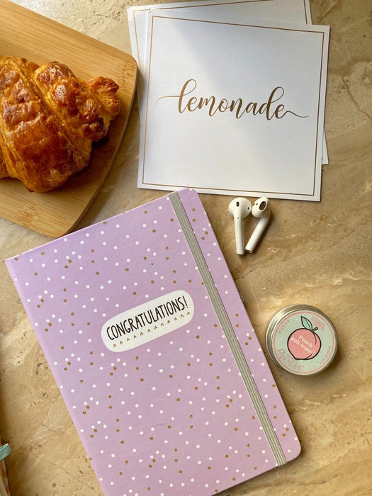 Notebook - With Elastic Enclosure - Congratulations-Description: This Congratulaiton Notebook by Lemonade is a perfect gift for all stationery lovers out there! The ruled pages make it easy for you to keep all your important notes, reminders even secret schemes all intact! Working hard? Back to school? Meeting bullets? We at Lemonade have a notebook for every occasion. It has 80 Ruled Pages (160 sides) and comes with an Elastic Pen Holder. Sold Individually. Dimensions: - Height - 8.25 InchesWid