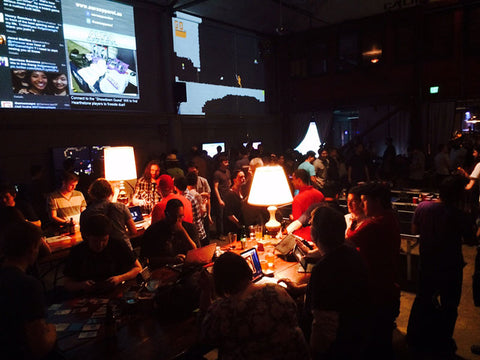 Games being played on tables lit by lamps while bystanders watch over on ShowDown Game Night at the Folsom Street Foundry.