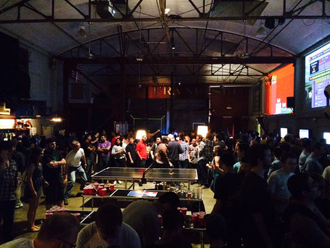 Crowd gathers around the table tennis game in the low light at the Folsom Street Foundry Game Night.