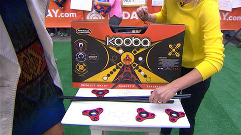 KOOBA game in it's packaging stands on a table surrounded by aeros and sticks to play the game with in the TODAY plaza.