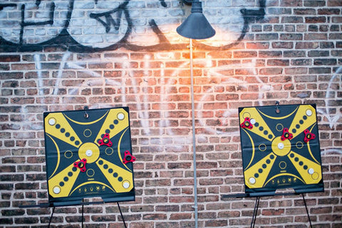 Two KOOBA game boards lined up against graffitied wall at sunset for party guests to play on SOHO rooftop in New York City.