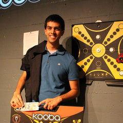 Joint third place KOOBA tournament finalist in front of the tournament board with his t-shirt and KOOBA Game prize.