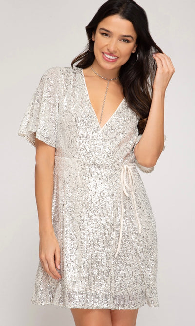 Get noticed in this cream sequin dress! Dress wraps around the front of the body and ties on the side. Perfect for holiday or wedding events!     Blush Sequin Wrap Mini Short Sleeve Dress with Front Tie. Blush stretchy knit lining. Imported. Blush Sequin stretchy knit self. V neckline. Short sleeves. Wrap around front detail with tie. Mini length. Self & Lining: 100% Polyester.