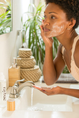 woman washes her face with rosehip oil cleanser