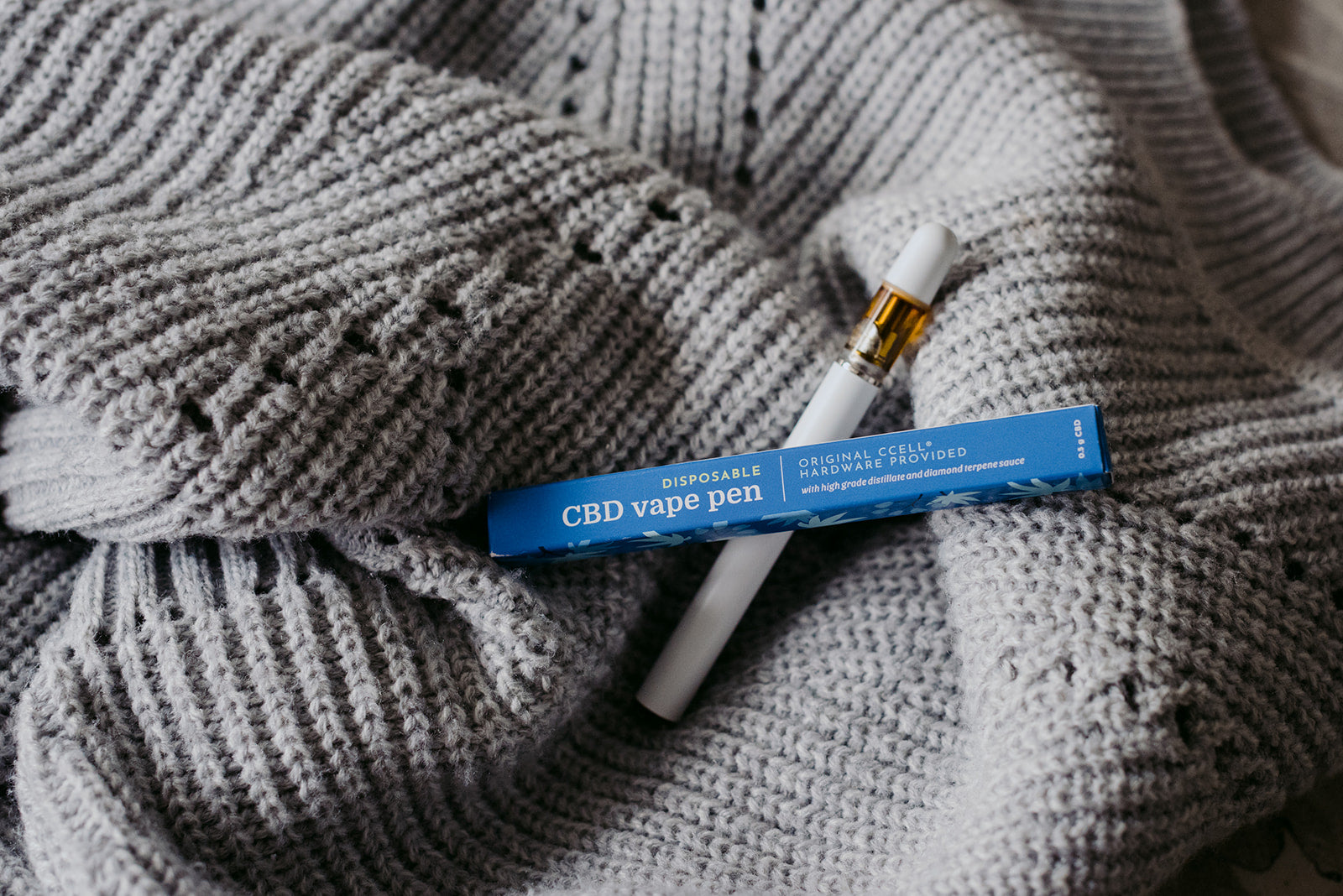CBD vape pen and packaging laying on a grey sweater