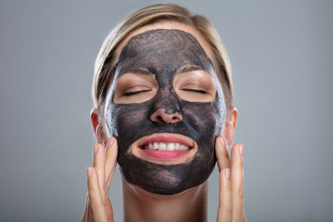 Close-up Of A Happy Woman Using Activated Charcoal Face Mask