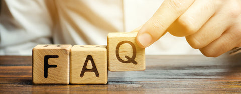 man puts wooden blocks with the word FAQ on a table