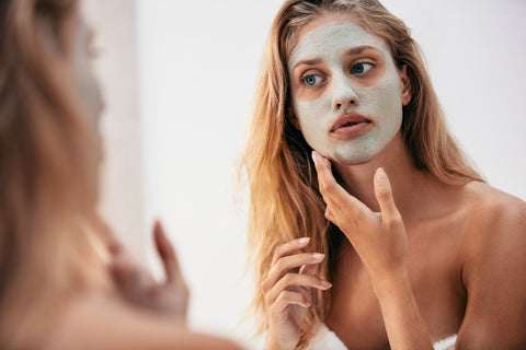 Woman looking in the mirror with mask on her face.
