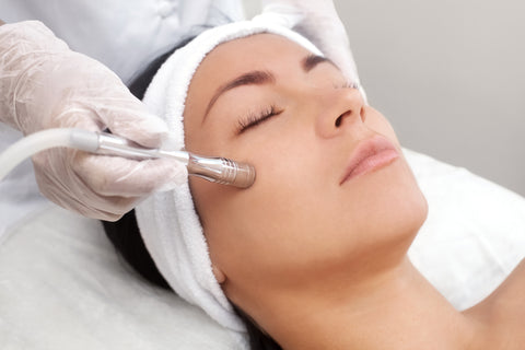 The cosmetologist makes the procedure Microdermabrasion of the facial skin of a beautiful, young woman