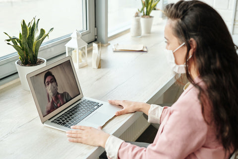 Woman sat at a desk wearing a fabric face masks having an online meeting on her laptop