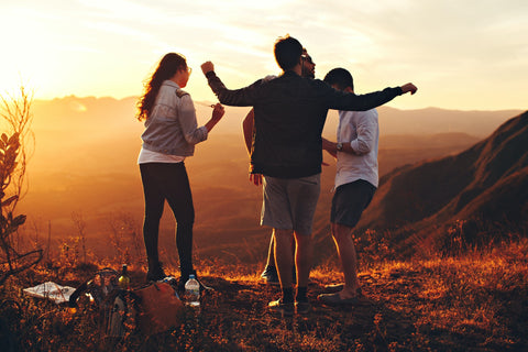 Three people dancing at sunset on top of a mountain.