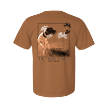 Load image into Gallery viewer, Printed on a Comfort Color terracotta colored t-shirt the point design is a dark and white colored pointer, head on, but its head is turned to find quail flying from left to right. In a field scene on a clear day.
