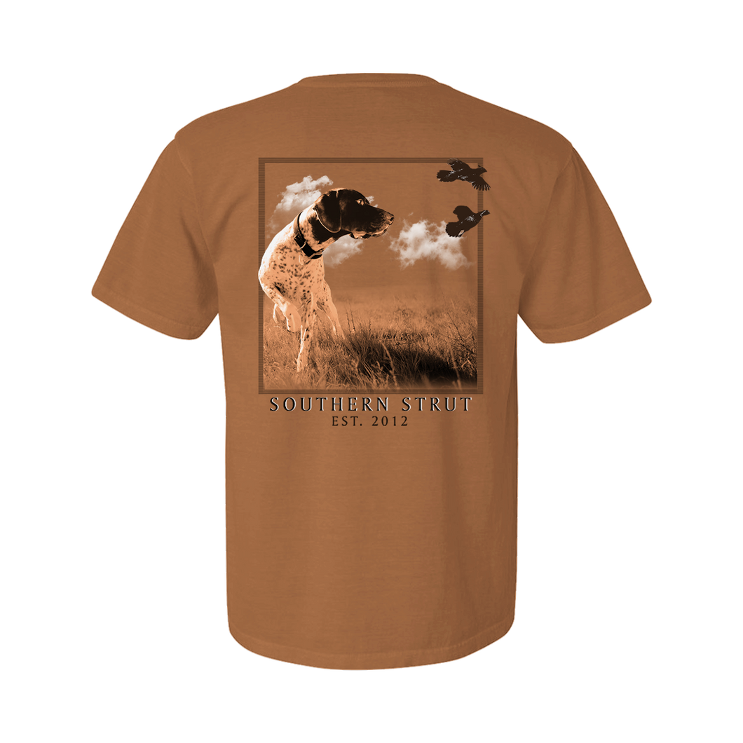 Printed on a Comfort Color terracotta colored t-shirt the point design is a dark and white colored pointer, head on, but its head is turned to find quail flying from left to right. In a field scene on a clear day.