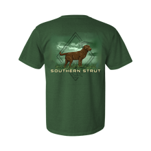 Load image into Gallery viewer, Printed on a Comfort Color light green colored t-shirt the brown lab design is a brown lab on an open grass field. Behind it is the Southern Strut left chest logo.