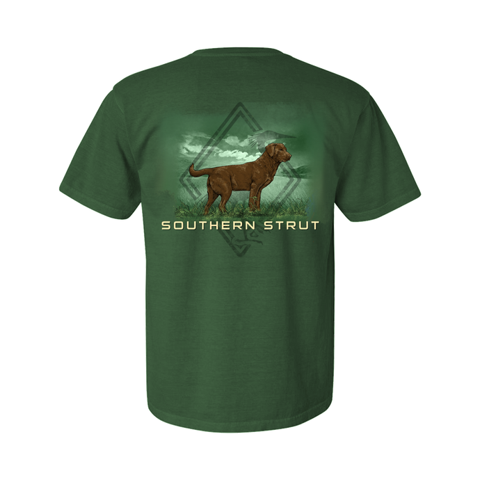 Printed on a Comfort Color light green colored t-shirt the brown lab design is a brown lab on an open grass field. Behind it is the Southern Strut left chest logo.