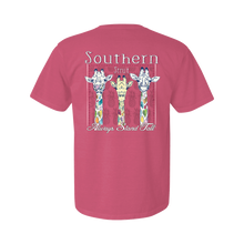 "Load image into Gallery viewer, Printed on a Comfort Color peony/pink color colored t-shirt the always stand tall shirt has 3 giraffes, the far left has it's tongue sticking our and the middle is the only one with bright yellow. All the giraffes have multi colored spots. ""Southern Strut"" is above the giraffe while ""Always Stand Tall"" is below."