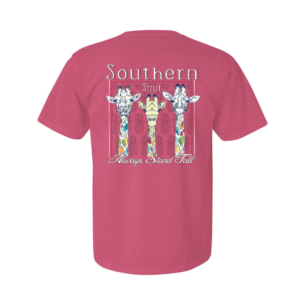 Printed on a Comfort Color peony/pink color colored t-shirt the always stand tall shirt has 3 giraffes, the far left has it's tongue sticking our and the middle is the only one with bright yellow. All the giraffes have multi colored spots.