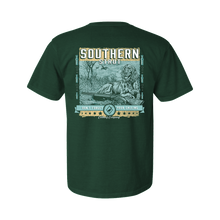 "Load image into Gallery viewer, Printed on a Comfort Color emerald colored t-shirt the Southern hunting design is an elegant english setter laying in a marsh patch, with an over and under shotgun laying in front. In the back, there are two ducks ascending. At the bottom, in a banner style, ""Don't Forget Your Calling"""