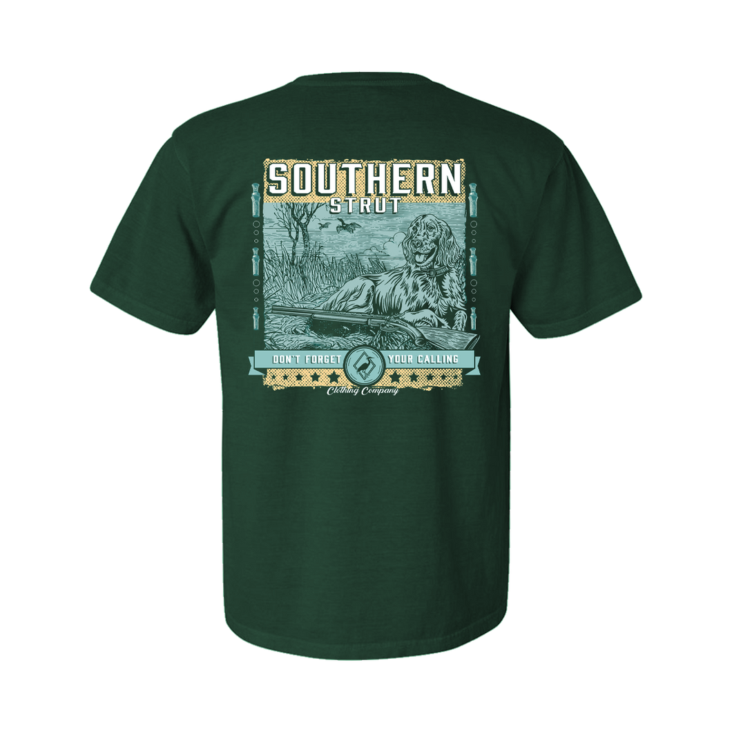 Printed on a Comfort Color emerald colored t-shirt the Southern hunting design is an elegant english setter laying in a marsh patch, with an over and under shotgun laying in front. In the back, there are two ducks ascending. At the bottom, in a banner style,