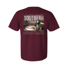 Load image into Gallery viewer, Printed on a Comfort Color vineyard colored t-shirt the decoy lake design is a wooden mallard decoy on a body of water, a lake in this case, with cattails and pinetrees in the back.