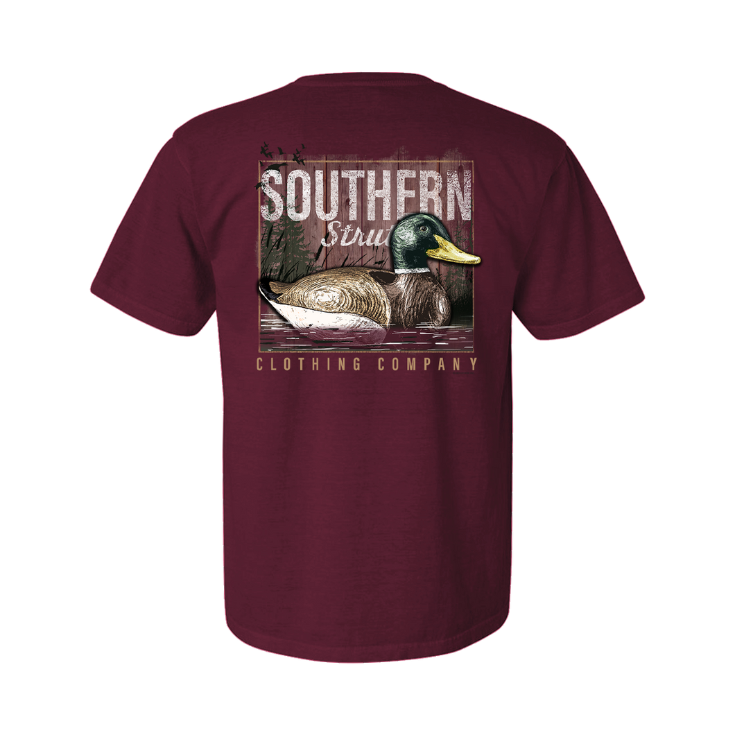 Printed on a Comfort Color vineyard colored t-shirt the decoy lake design is a wooden mallard decoy on a body of water, a lake in this case, with cattails and pinetrees in the back.