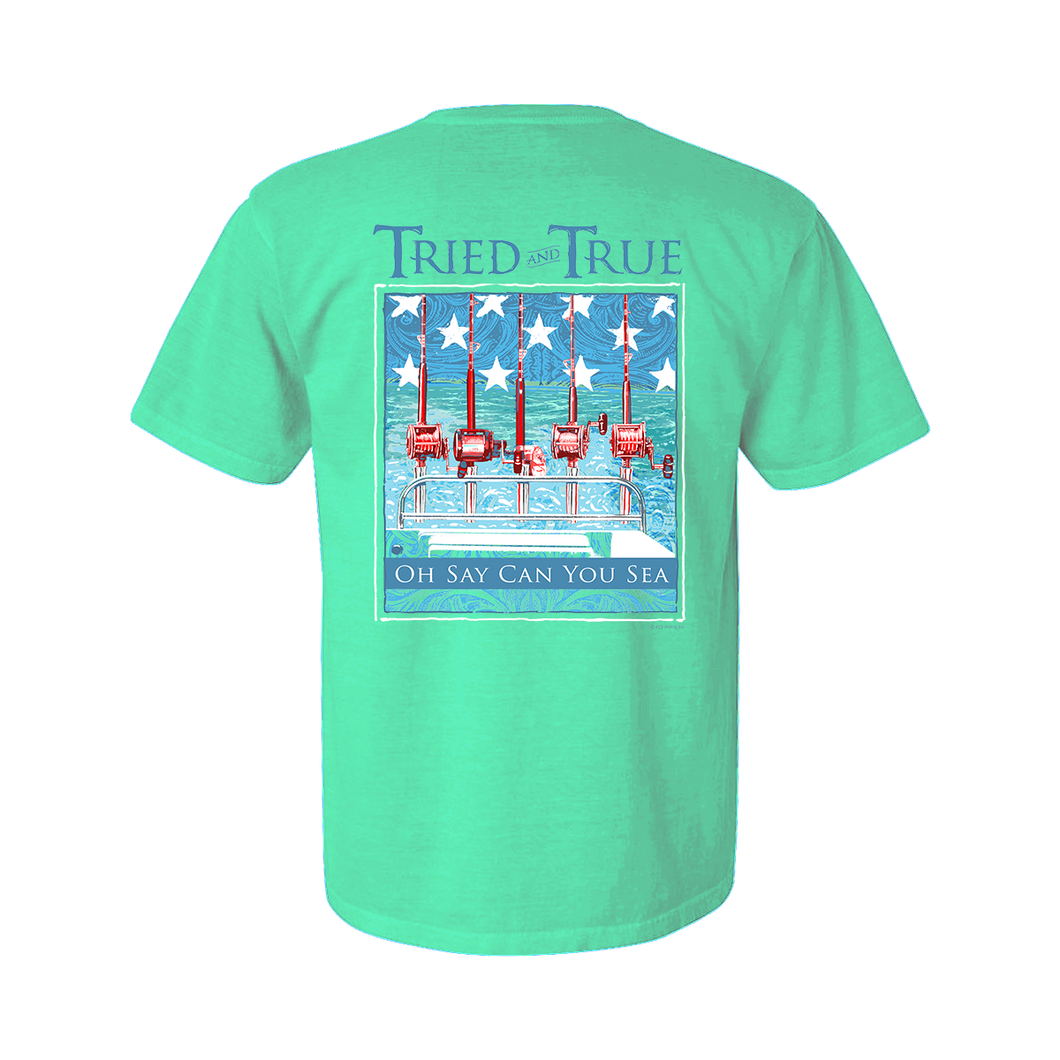Printed on a Comfort Color seafoam colored t-shirt, the Oh Say Can You Sea, an Americana themed, design is an off shore theme of a an offshore boat in the middle of sea with a blue back ground with white stars and red reels on the back.
